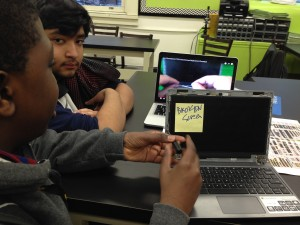 Students begin taking a broken screen off a chromebook